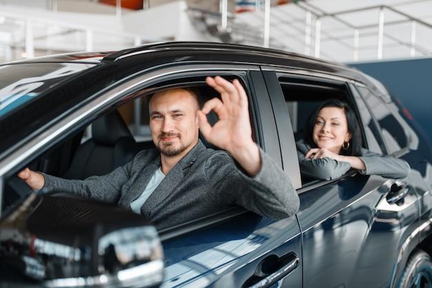 Glückliches paar fährt mit neuem auto vom ausstellungsraum ab.