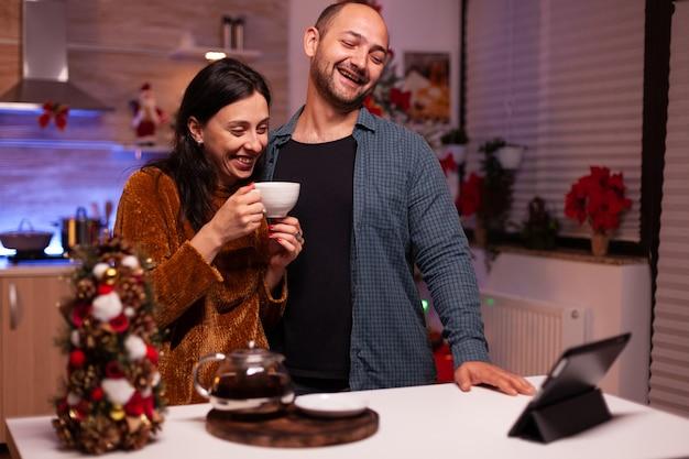Glückliches paar feiert weihnachtsferien mit entfernten freunden während des online-videoanrufs