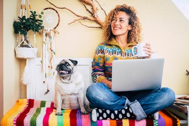 Glückliches paar frau und lustiger hund zu hause sitzen auf einer farbigen abdeckung haben spaß und verwenden technologie-laptop-computer