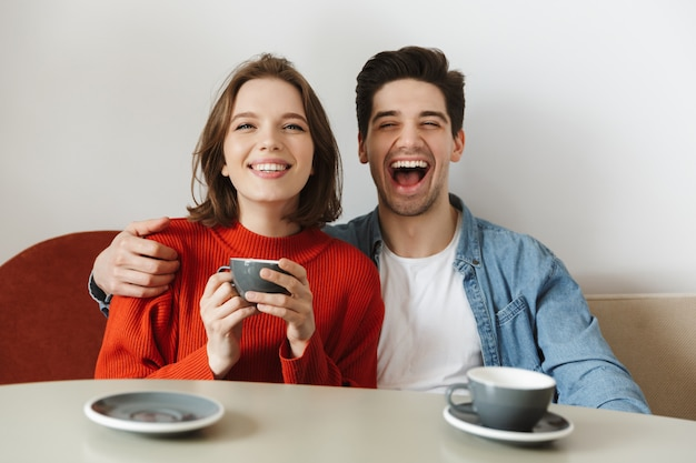 Glückliches paar frau und mann lachen, während im café ruhen und kaffee oder tee zusammen trinken