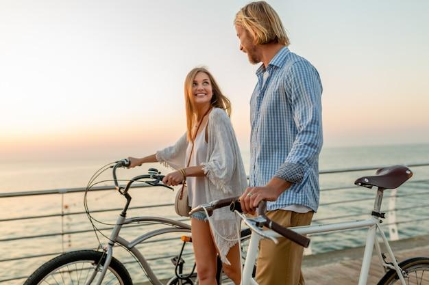 Glückliches paar freunde, die im sommer auf fahrrädern reisen