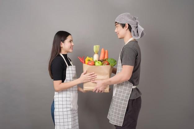 Glückliches paar hält gemüse in der grauen wand der einkaufstüte