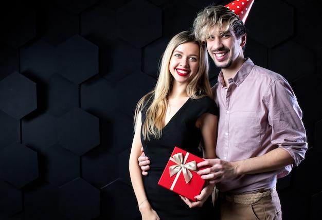 Glückliches paar halten rote geschenkbox, mann und frau lächeln, die kamera umarmend betrachten, auf schwarzem hintergrund. feier und romantisches konzept.