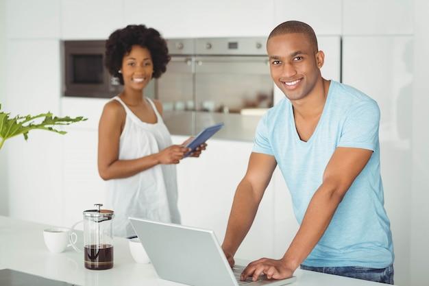 Glückliches paar herein in der küche unter verwendung des laptops und der tablette