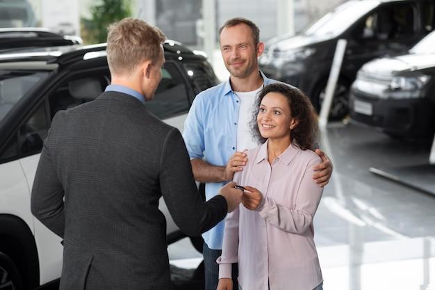 Glückliches paar im autohaus autohaus