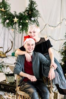 Glückliches paar im geschmückten raum mit weihnachtsbaum