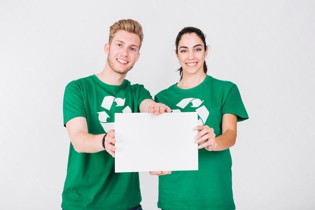 Glückliches paar im grünen t-shirt, das leeres weißes plakat hält