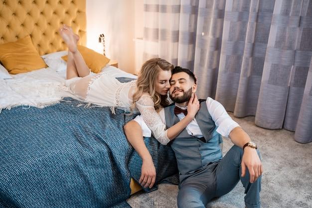 Glückliches paar im luxusschlafzimmer in ihrem hochzeitstag.