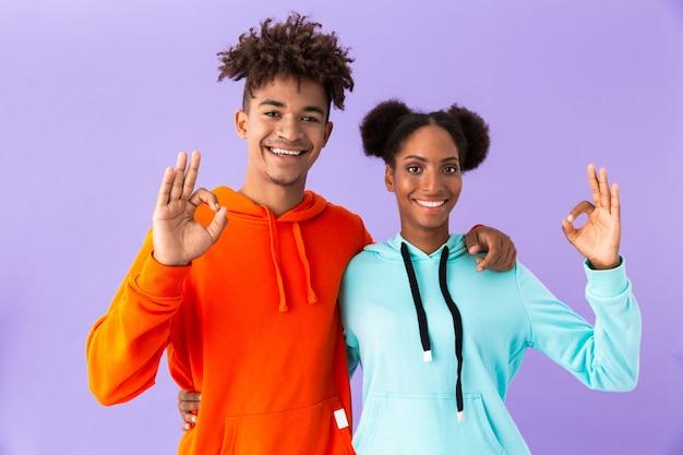 Glückliches paar in bunten kleidern, die ok zeichen zeigen, lokalisiert über violetter wand