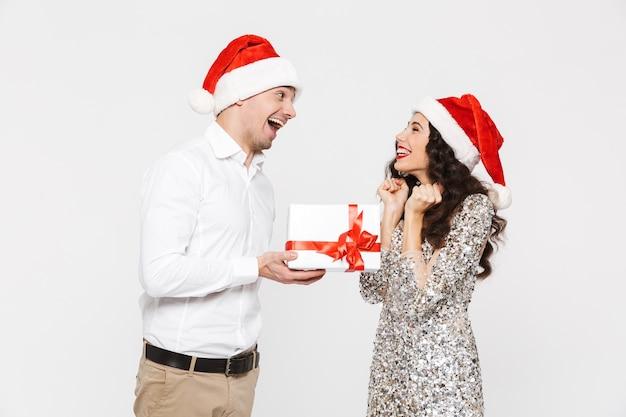 Glückliches paar in den roten hüten, die neujahr feiern, isoliert über weiß, austausch mit geschenken