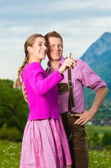 Glückliches paar in der alpenwiese in tracht