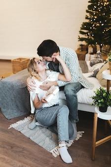 Glückliches paar in der liebe, die auf dem bett sitzt und geschenke durch den weihnachtsbaum in einem gemütlichen haus gibt