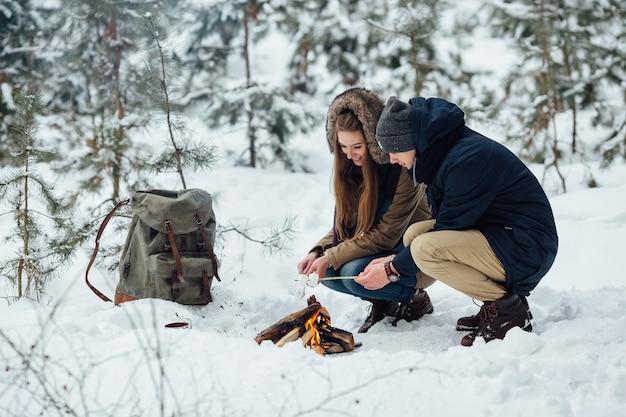 Glückliches paar in der liebe, die eibische über einem lagerfeuer im winter des verschneiten winters brät.