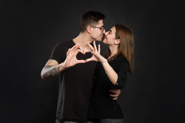 Glückliches paar in der liebe, die herz mit ihren fingern zeigt. nahaufnahme des paares, das herzform mit händen macht.
