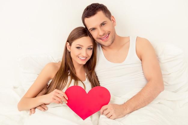Glückliches paar in der liebe, die im bett liegt und rotes papierherz hält