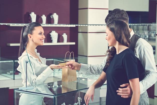 Glückliches paar in der liebe, die mit kreditkarte im juweliergeschäft zahlt