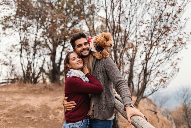 Glückliches paar in der liebe, die schöne aussicht umarmt und betrachtet. mann hält auf dem rücken ihren aprikosenpudel. herbstzeit.