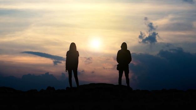 Glückliches paar in der liebessilhouette von liebeskerl und -mädchen gegen sonnenuntergang