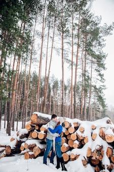 Glückliches paar in der liebesumarmung im kalten wald des verschneiten winters, im kopienraum, in der parteifeier des neuen jahres, im feiertag und in den ferien, in der reise, in der liebe und in den beziehungen