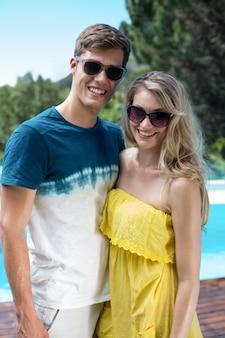 Glückliches paar in der sonnenbrille, die nahe dem pool steht