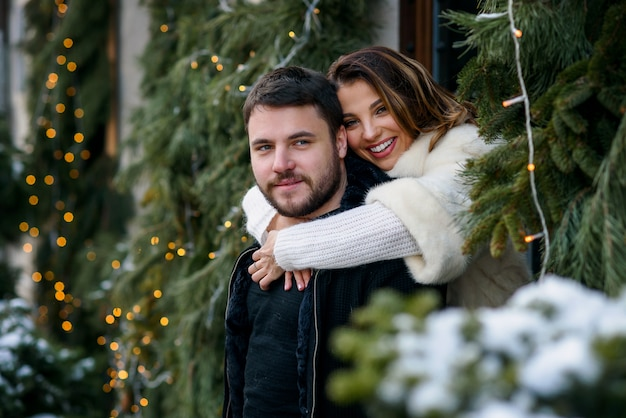 Glückliches paar in der warmen kleidung, die auf dem weihnachtsbaum mit lichtern sich umarmt. winterferien, weihnachten und neujahr.