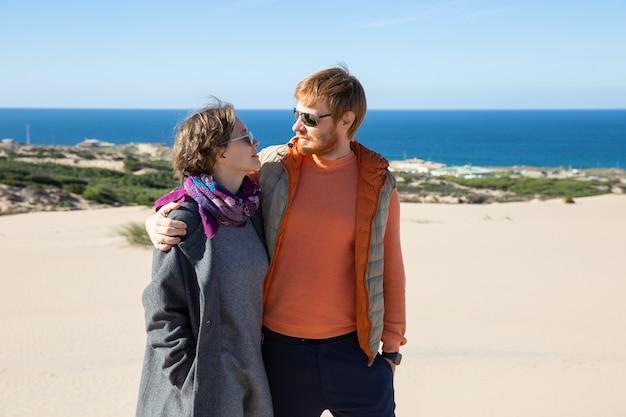 Glückliches paar in der warmen kleidung, die auf sand umarmt und geht und freizeit auf see verbringt