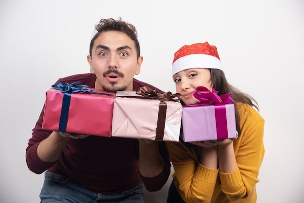 Glückliches paar in der weihnachtsmannmütze mit weihnachts- und neujahrsgeschenk.