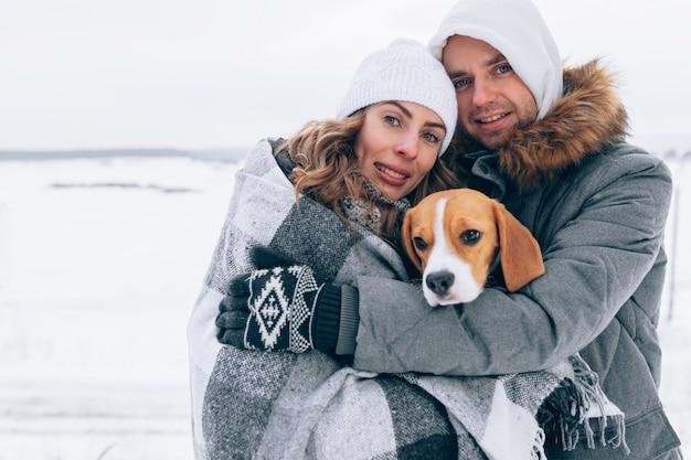 Glückliches paar in der winterlandschaft glückliche familie mit beagle-hund. wintersaison