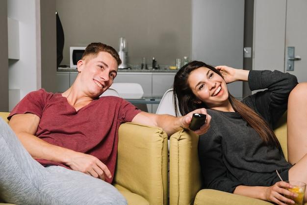 Glückliches paar in sesseln vor dem fernseher