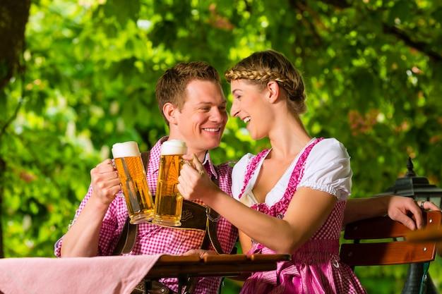 Glückliches paar in trinkendem bier des biergartens