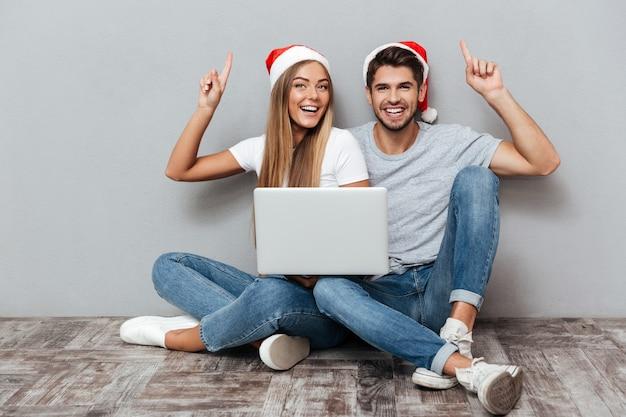 Glückliches paar in weihnachtsmützen mit laptop