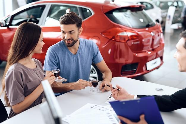 Glückliches paar kam, um ihr auto zu wählen.