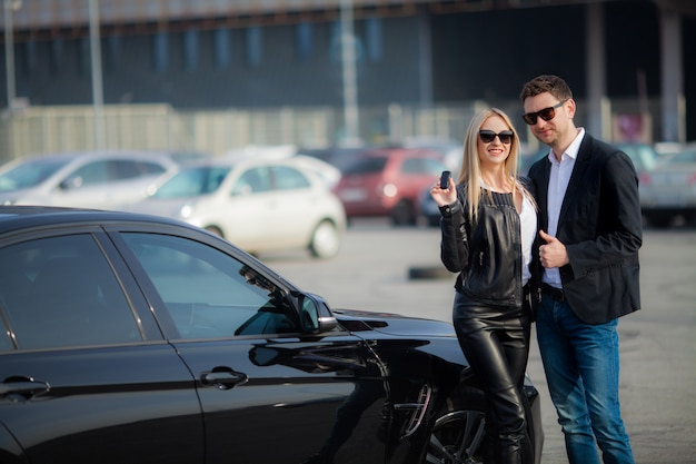 Glückliches paar kaufen neues modernes schwarzes auto