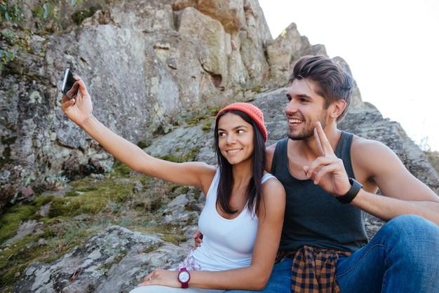 Glückliches paar macht selfie und sitzt auf felsen. mädchen hält das telefon