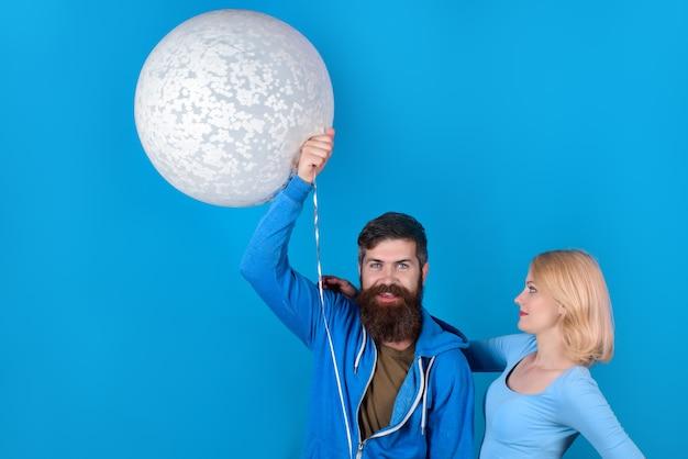 Glückliches paar mit ballonfrauen, die den stilvollen kerl der ehemannfamilie umarmen, hält großen ballon modisch
