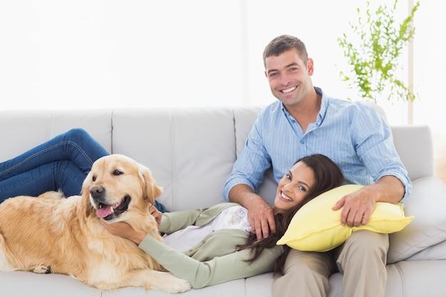 Glückliches paar mit dem hund, der auf sofa sich entspannt