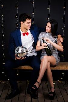 Glückliches paar mit discokugel und flasche champagner