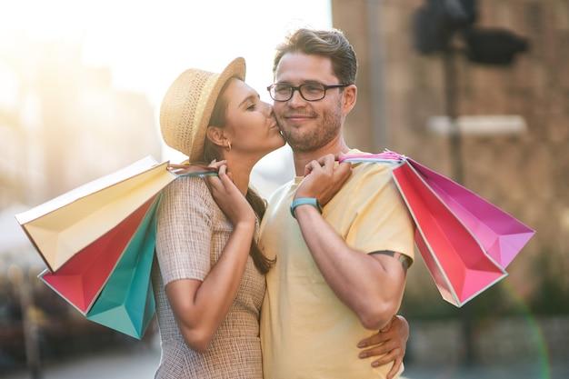 Glückliches paar mit einkaufstüten in der stadt