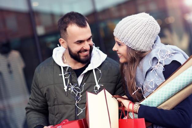 Glückliches paar mit einkaufstüten nach dem einkaufen in der stadt lächelnd und umarmt