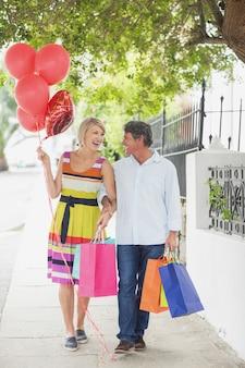 Glückliches paar mit einkaufstüten und luftballons
