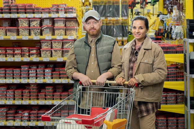 Glückliches paar mit einkaufswagen, das gegen displays mit nägeln und anderen haushaltswaren steht