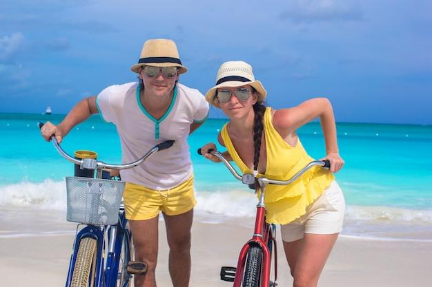 Glückliches paar mit fahrrädern im sommer karibik urlaub