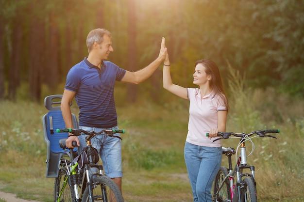 Glückliches paar mit fahrrädern spaß im kiefernwald, romantischer spaziergang auf fahrrädern. mann und frau mit fahrrädern im park, radfahren am sommertag. sonnenlicht