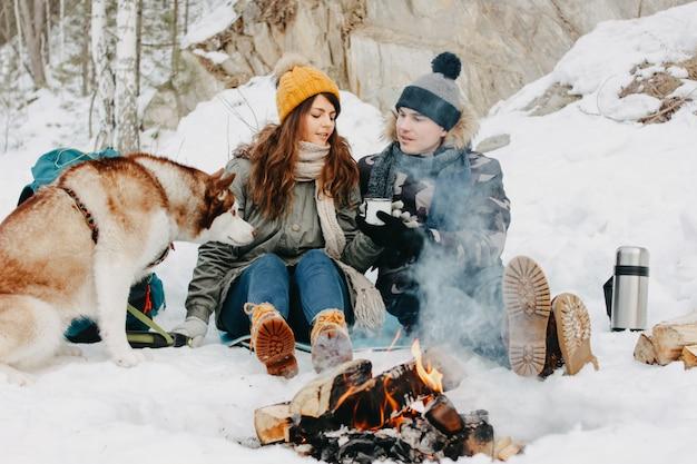 Glückliches paar mit hund haski am waldnaturpark in der kalten jahreszeit.