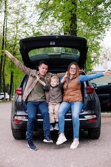 Glückliches paar mit ihrem kleinen sohn im offenen kofferraum des geländewagens auf dem parkplatz