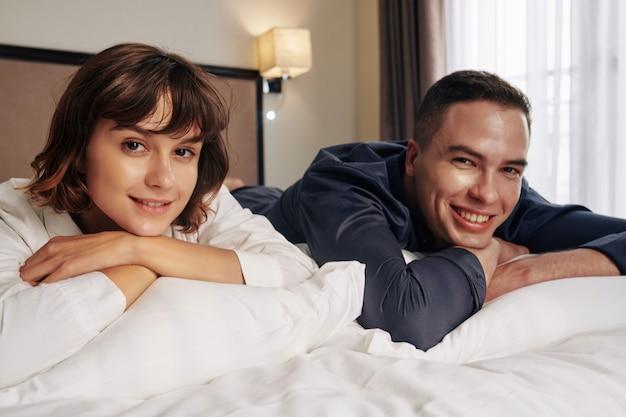 Glückliches paar mit im schlafanzug, der auf bett ruht