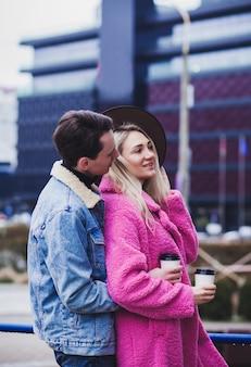 Glückliches paar mit kaffee während des spaziergangs in der stadt. foto im freien des glücklichen jungen paares, das datum genießt
