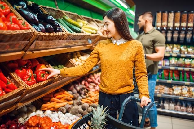 Glückliches paar mit korb im supermarkt zusammen