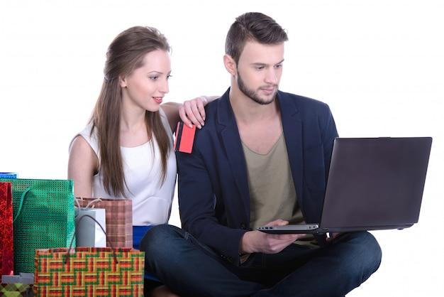 Glückliches paar mit kreditkarte online einkaufen.