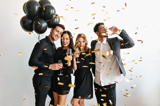 Glückliches paar mit luftballons, die jubiläum mit ihren freunden feiern